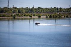 一条小船沿河航行在一个夏天晴天 免版税库存图片