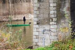 一条小船的一位孤立渔夫在桥梁下 免版税库存图片