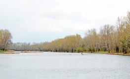 一条小船的一位孤立渔夫有马达的,钓鱼在森林河 秋天 图库摄影