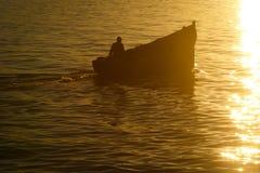 一条小船的一位渔夫在黎明 库存图片