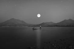 一条小船的一位渔夫有浪漫夜风景的 免版税库存照片