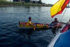 一条小船的两个埃及孩子接近另一条小船谈话,使用木板作为桨 库存照片