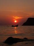 一条小船的二个人在日落 免版税库存图片
