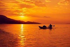 一条小船的人在日落的海 免版税库存照片