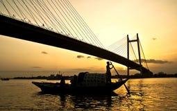 一条小船的人在日落 免版税库存图片