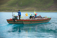 一条小船的人在Yamdrok湖 库存照片