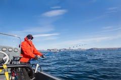 一条小船的人有一根钓鱼竿的 红色夹克 免版税库存照片