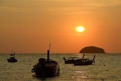 一条小船的剪影反对红色天空和热带日落的 免版税库存图片