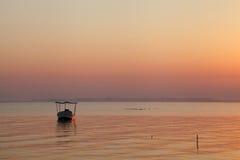 一条小船的剪影在日出期间的在Busaiteen海滩 免版税图库摄影
