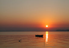 一条小船的剪影在日出期间的 免版税库存照片