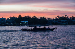 一条小船的剪影在芹苴市河日出的,越南的 免版税库存照片