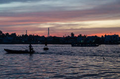 一条小船的剪影在芹苴市河日出的,越南的 库存照片
