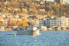 一条小船的场面在湖的在晴天有都市背景 库存照片