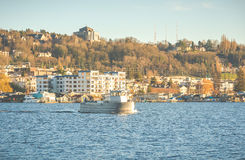 一条小船的场面在湖的在晴天有都市背景 图库摄影