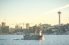 一条小船的场面在湖的在晴天有都市背景 免版税库存图片