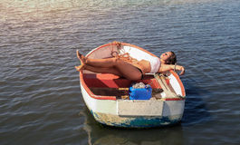 一条小船的女性在日落 库存照片