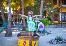 一条小船的小美丽的女孩在海滩在 免版税库存图片