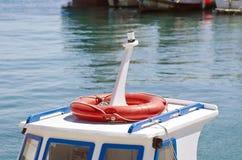 一条小船的屋顶有橙色lifebuoy的在港口 免版税库存照片