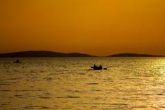 一条小船的日落剪影在湖的 库存图片