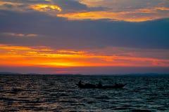 一条小船的日落剪影在湖的 免版税库存图片