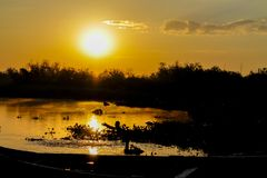 一条小船的日落剪影在湖的 库存照片