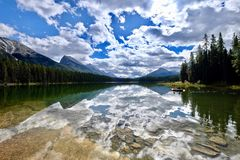 一条小船的朋友在美丽的湖 山和云彩反射在镇静水中 库存照片