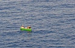 一条小船的渔夫向抓住求助 免版税库存照片