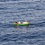 一条小船的渔夫向抓住求助 免版税库存图片