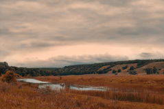 一条小船的渔夫在一个多云多小山谷的一个小湖 库存照片