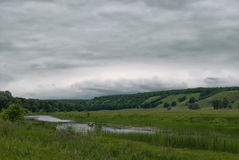 一条小船的渔夫在一个多云多小山谷的一个小湖 库存图片