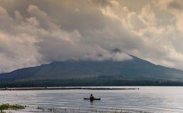一条小船的渔夫在一座山的背景在云彩的 图库摄影