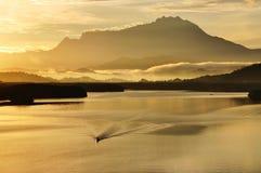 一条小船的渔夫在日出 库存照片