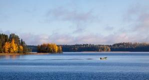 一条小船的渔夫在湖 免版税库存照片