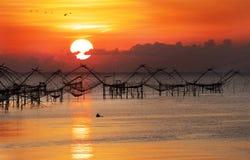 一条小船的渔夫对他们的捕鱼网在早晨 免版税库存图片