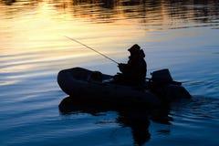 一条小船的渔夫有在河的一根钓鱼竿的日落的 免版税库存照片