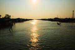 一条小船的渔夫有在泰国的日落的 库存照片