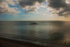 一条小船的渔夫海上 与云彩的风景天空 Pandan,班乃岛,菲律宾 免版税库存照片