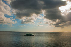 一条小船的渔夫海上 与云彩的风景天空 Pandan,班乃岛,菲律宾 免版税库存图片