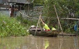 一条小船的男孩在湄公河 免版税库存照片