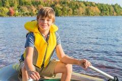 一条小船的男孩在水中 库存图片