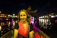 一条小船的白种人女孩在晚上在会安市,越南 库存照片