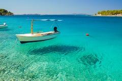 一条小船的美丽如画的场面在Milna一个安静的海湾的在Brac海岛,克罗地亚上的 库存照片