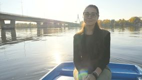 一条小船的迷人的女孩在太阳的光芒的背景 在他的面孔的美好的微笑 美好的安排 慢的行动 股票录像