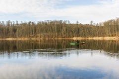 一条小船的钓鱼者在湖 免版税库存照片