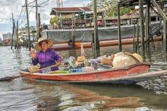 一条小船的销售妇女在浮动市场上 免版税库存照片