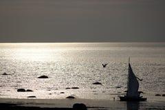 一条小船的阴影由海的日落的 库存图片