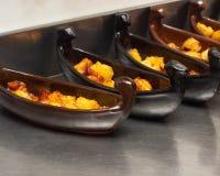 一条小船的餐馆盘用在一个深炸锅油煎的一个金黄外壳的土豆 特写镜头,用小锄头 库存图片