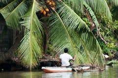 一条小船的Sri Lankian渔夫在河 库存图片