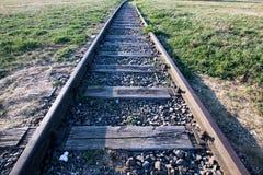 一条废弃的铁路的路轨与草和木睡眠者的 老R 图库摄影