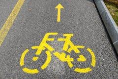 一条循环的道路的黄色箭头和自行车标志 库存照片